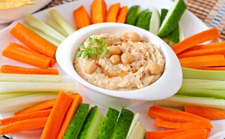 Hummus otoczony słupkami marchwi i ogórka