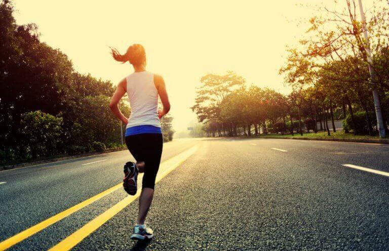 Kobieta biegnąca po drodze w zachodzącym słońcu