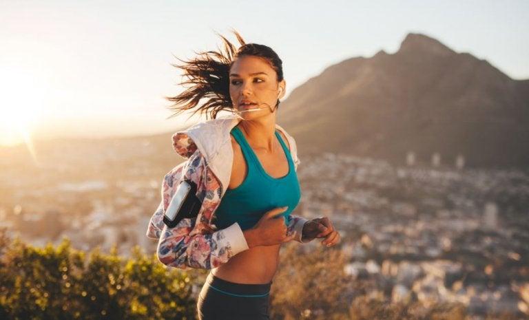 Kobieta biegnąca po górach, w tle miasto
