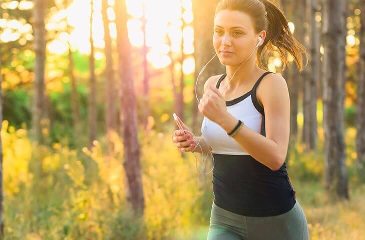 Kobieta biegnąca po lesie i słuchająca muzyki - piosenki z lat 90-tych do biegania