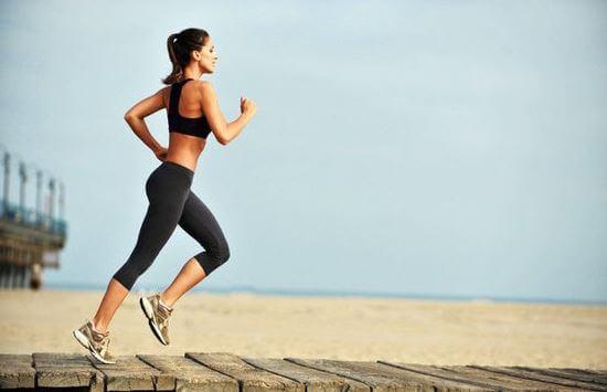Kobieta biegnąca w słońcu po podeście na plaży