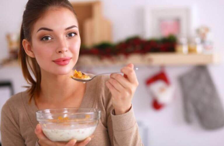 Kobieta jedząca z miski płatki śniadaniowe z mlekiem