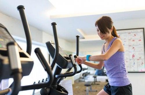 Kobieta na orbitreku mierzy czas treningu