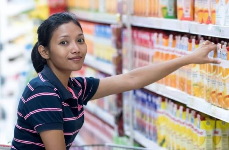Kobieta w sklepie sięgająca po sok na regale
