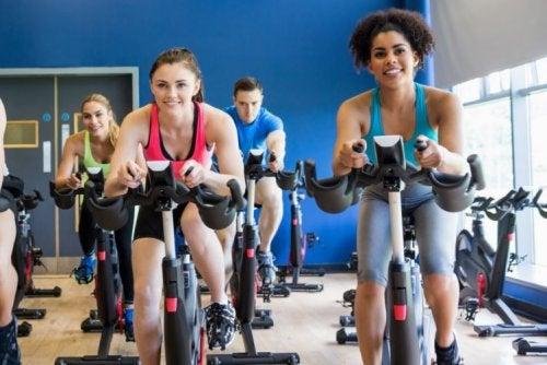 Osoby ćwiczą w grupie na rowerze stacjonarnym