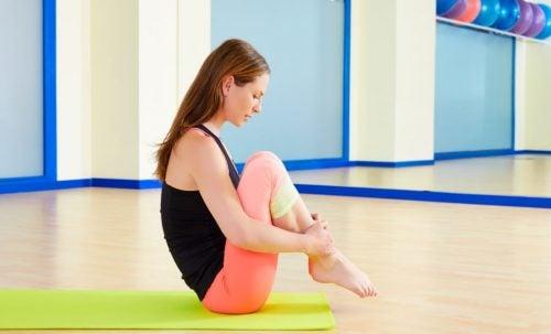 Kobieta siedząca na macie i ćwicząca pilates