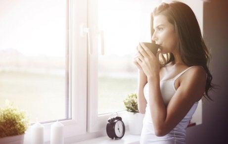 kobieta pijąca kawę w oknie i czekająca na poranny trening