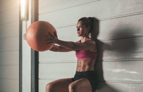 Kobieta z piłką robiąca przysiad izometryczny
