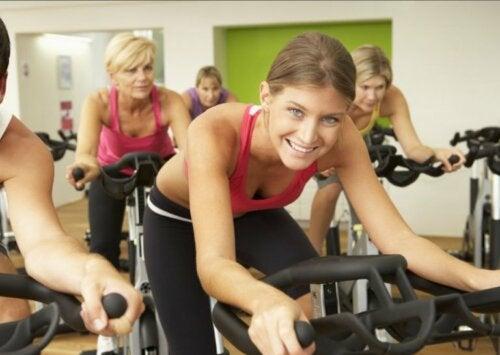 Uśmiechnięte kobiety uprawiające intensywny spinning na sali