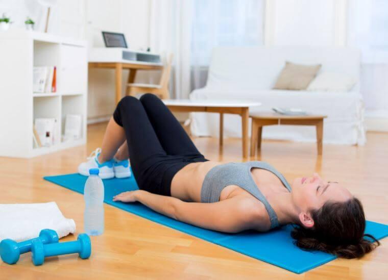 Zmęczona kobieta leżąca na plecach na macie - jak zyskać wyrzeźbione mięśnie brzucha?