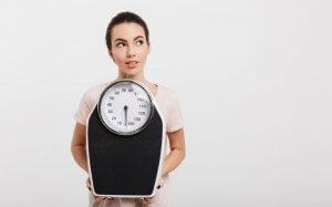 błędy w odchudzaniu - kobieta z wagą