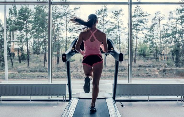 Kobieta biegnąca na bieżni w pokoju z widokiem na las