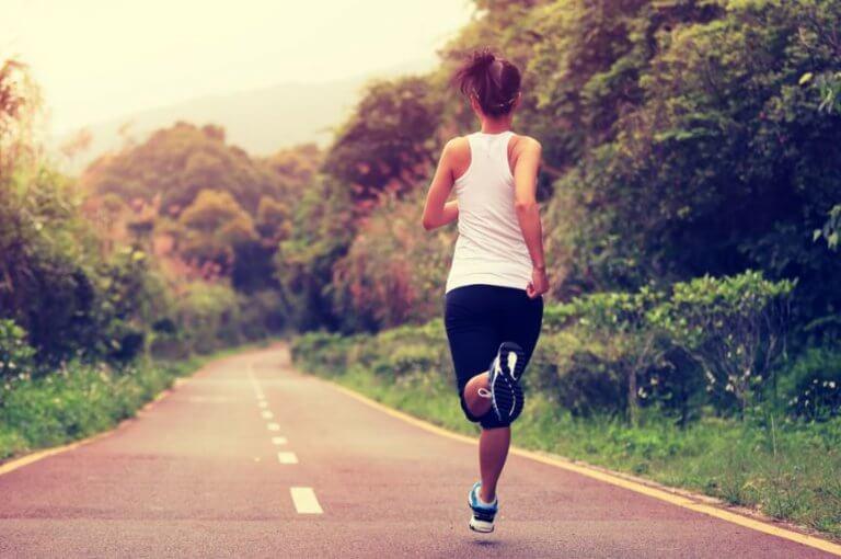 Kobieta biegnąca po jezdni pośród lasu - bieganie samemu