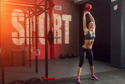 Kobieta ćwicząca z kettlebellem na siłowni - ćwiczenia CrossFit