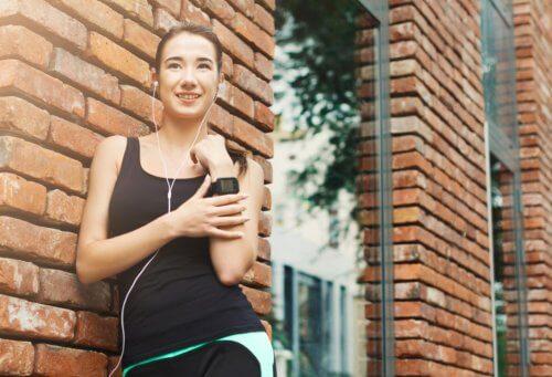 Kobieta opierająca się o budynek z cegły
