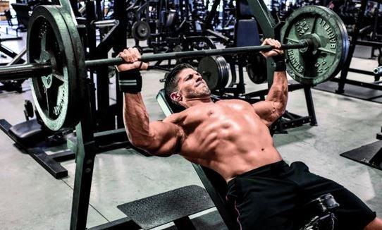 Trening klatki piersiowej - Mężczyzna wyciskający sztangę na ławeczce ukośnej - ćwiczenia na dolne partie klatki piersiowej