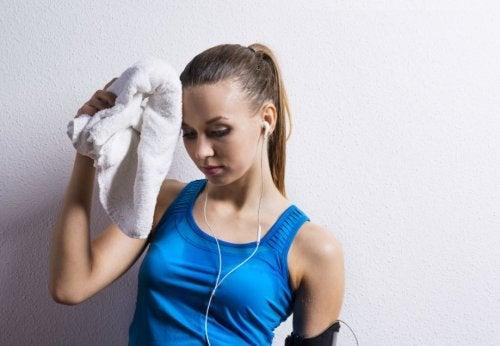 pocenie się - spocona kobieta po treningu w niebieskiej koszulce