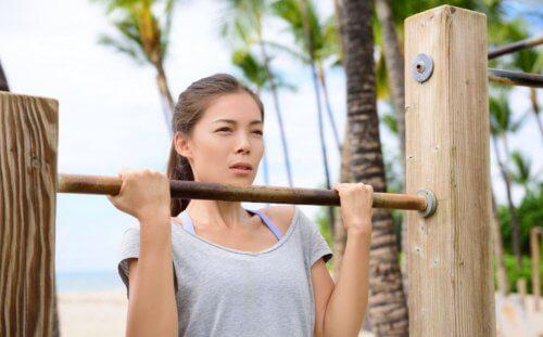 podciąganie się - kobieta na drewnianym drążku