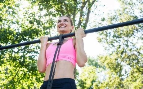 podciąganie się - uśmiechnięta kobieta podciągająca się