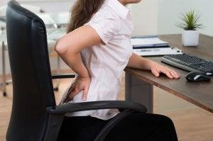problemy z kręgosłupem - kobieta z bólem krzyża przy komputerze