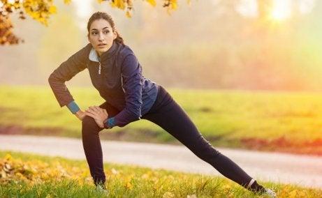 rozciąganie po treningu - kobieta rozciągająca się w parku