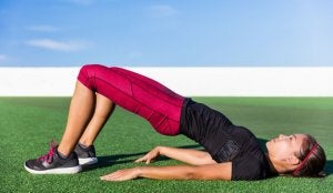 rozciąganie kręgosłupa - kobieta robiąca półmostek na trawie
