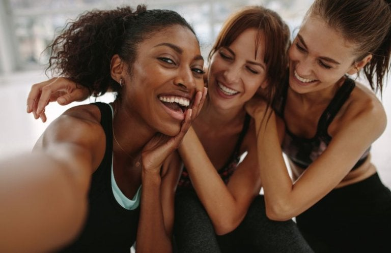 Trzy roześmiane kobiety w strojach sportowych robiące sobie selfie