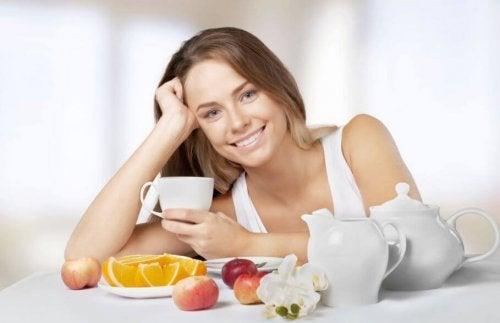 Uśmiechnięta kobieta przy stole z herbatą i owocami - jak przyspieszyć przemianę materii