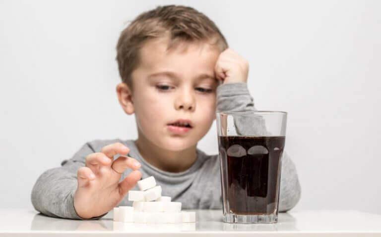 Chłopiec sięgający po szklankę z colą - słodkie napoje są złe dla organizmu