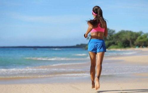 Kobieta biegnąca boso po plaży ćwiczy kardio o umiarkowanej intensywności