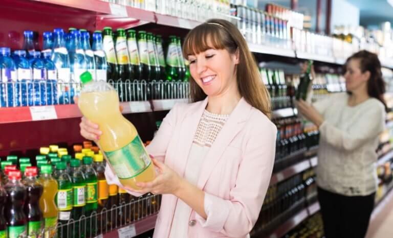 Kobieta czytająca w sklepie etykietę napoju