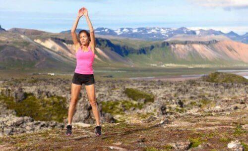 Kobieta robiąca przysiady z wyskokiem na zewnątrz w górach ćwiczenia opracowujące pośladki i nogi
