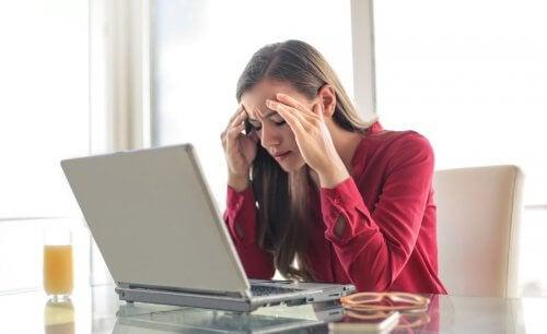 Kobieta siedząca przed laptopem i masująca skronie - odwodnienie i ból głowy