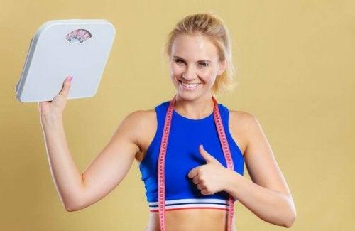 Kobieta trzymająca wagę, pokazująca kciuk do góry - dieta ketogeniczna pozwoli schudnąć
