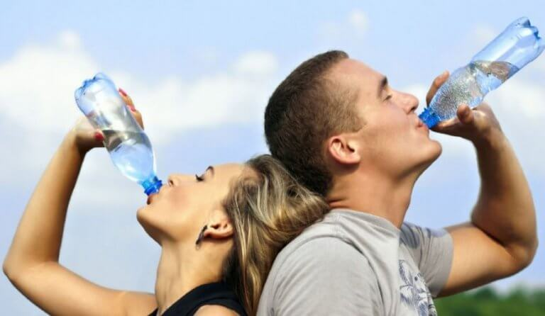 Mężczyzna i kobieta obróceni plecami do siebie i pijący wodę - opanuj ból głowy