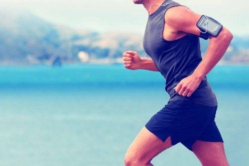 Mężczyzna biegnący po plaży z komórką na ramieniu