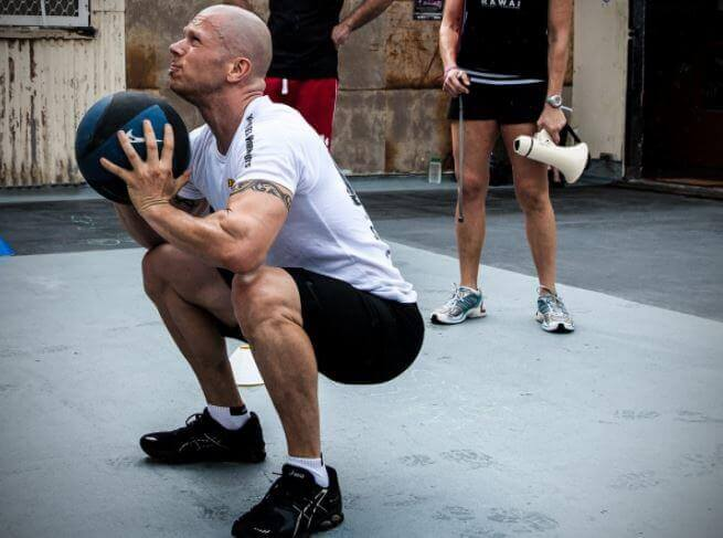 Mężczyzna robiący przysiady z piłką - ćwiczenia z piłką lekarską
