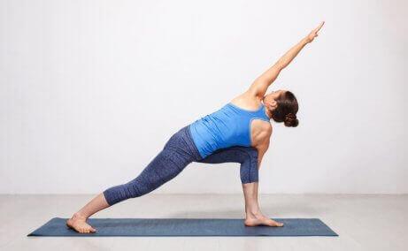 pozycje w jodzie - kobieta robiąca pozycję odwróconego trójkąta