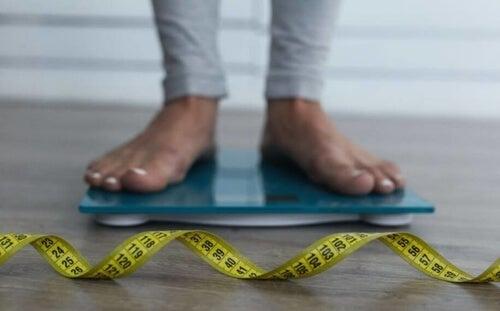 osoba stojąca na wadze, przed nią leży centymetr krawiecki - błonnik