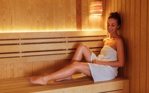 Kobieta siedząca na ławce w saunie - zalety sauny