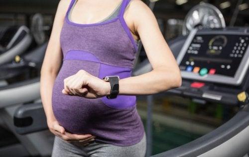 Kobieta w ciąży przy bieżni patrząca na zegarek - bieganie w ciąży