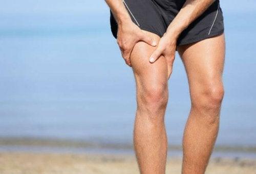 Mężczyzna ściskający udo - skurcze mięśni