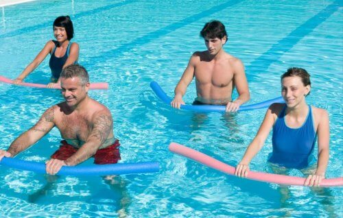 Osoby ćwiczące w basenie z makaronem