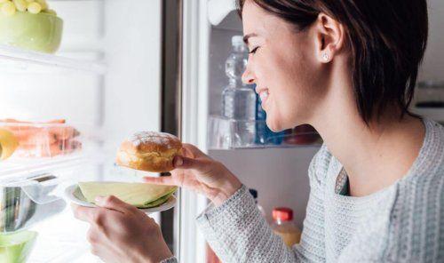 źle zbilansowana dieta może prowadzić do podjadania - kobieta jedząca pączka