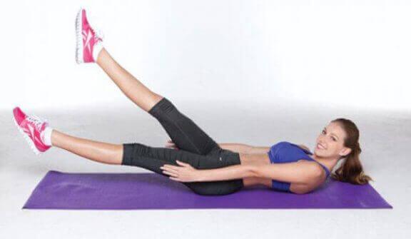 kobieta robi nożyce - ćwiczenie brzucha