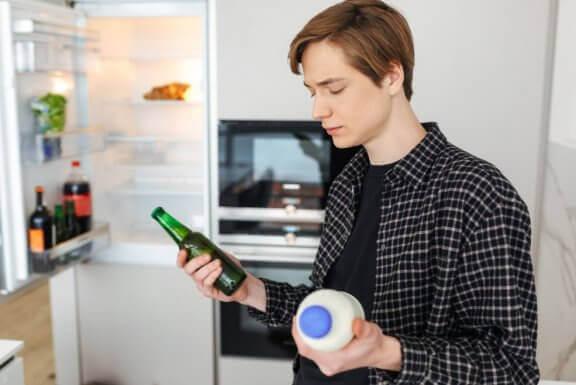 Mężczyzna trzymający w jednej ręce piwo a w drugiej mleko - czy piwo nawadnia?