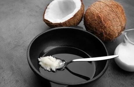 olej kokosowy na łyżeczce i rozłupany kokos
