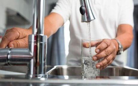 woda z kranu - mężczyzna nalewa wodę do szklanki
