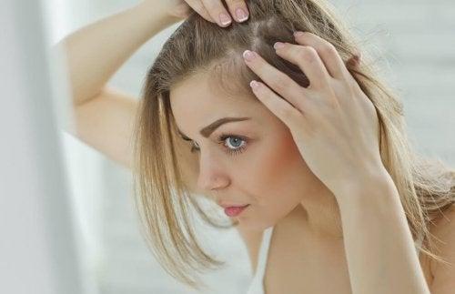 Kobieta przyglądająca się swoim włosom - jak dbać o włosy na siłowni