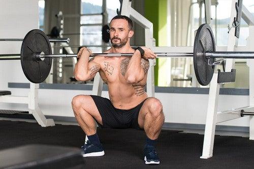 Mężczyzna robiący przysiady ze sztangą z przodu ćwiczenia CrossFit